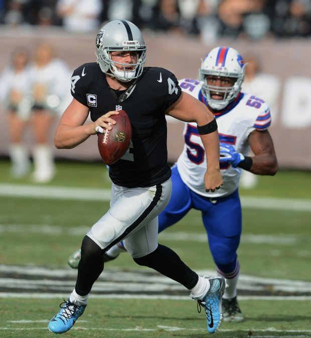 The Oakland Raiders' Derek Carr (4) rolls out against the Buffalo Bills in the first half of their NFL game at the Oakland Coliseum in Oakland, Calif., on Sunday, Dec. 4, 2016. (Dan Honda/Bay Area News Group)