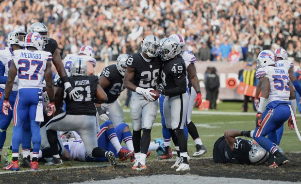 The Oakland Raiders' Latavius Murray (28) and Jamize Olawale (49) celebrate a touchdown against the Buffalo Bills in the second half of their NFL game at the Oakland Coliseum in Oakland, Calif., on Sunday, Dec. 4, 2016. (Dan Honda/Bay Area News Group)
