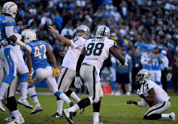 SAN DIEGO, CA - DECEMBER 18: Kicker Sebastian Janikowski #11 of the Oakland Raiders kicks the game winning field goal as punter Marquette King #7 holds en route to the Raiders 19-16 win over the San Diego Chargers at Qualcomm Stadium on December 18, 2016 in San Diego, California. (Photo by Donald Miralle/Getty Images)