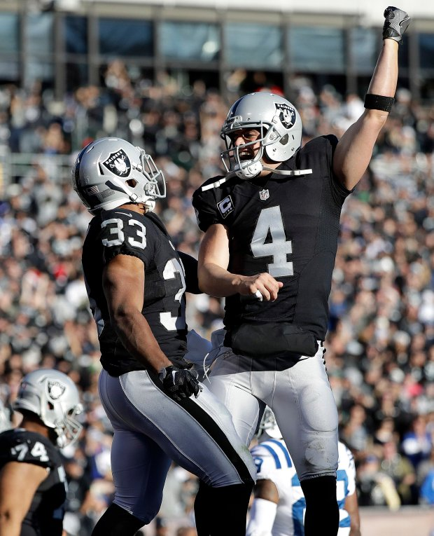Oakland Raiders running back DeAndre Washington (33) celebrates after running for touchdown with quarterback Derek Carr (4) during the second half of an NFL football game against the Indianapolis Colts in Oakland, Calif., Saturday, Dec. 24, 2016. (AP Photo/Marcio Jose Sanchez)