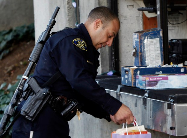 2012 file photograph: San Jose police officer Bruce Barthelemy picks up gift bags to hand out during his Christmas Eve shift.