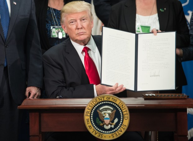 TOPSHOT - US President Donald Trump signs an executive order to start the Mexico border wall project at the Department of Homeland Security facility in Washington, DC, on January 25, 2017. / AFP PHOTO / NICHOLAS KAMMNICHOLAS KAMM/AFP/Getty Images