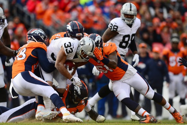 Running back DeAndre Washington #33 of the Oakland Raiders is tackled by outside linebacker Von Miller #58 and inside linebacker Todd Davis #51 of the Denver Broncos in the first quarter at Sports Authority Field at Mile High on January 1, 2017 in Denver, Colorado. (Photo by Dustin Bradford/Getty Images)