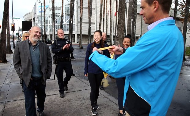 Seven weeks after collapsing with a heart attack while running in the Turkey Trot race, Mike Dosik, left, finishes the race receiving a medal from Chris Weiler of the Silicon Valley Turkey Trot Wednesday, Jan. 11, 2017, in San Jose, Calif. Dose was joined by the nurses, police and rescue personnel who helped save his life that Thanksgiving Day. (Karl Mondon/Bay Area News Group)