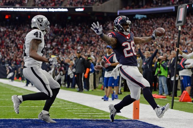 Houston Texans' Lamar Miller (26) scores a touchdown past Oakland Raiders' Brynden Trawick (41) in the first quarter of the AFC West Wild Card round game at the NRG Stadium in Houston, Texas, on Saturday, Jan. 7, 2017. (Jose Carlos Fajardo/Bay Area News Group)