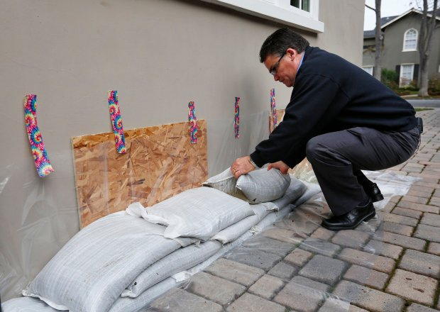 In this file photo, Jon Hospitalier, Palo Alto assistant director of public works, demonstrates proper sandbagging techniques using plywood, polyethylene plastic sheeting, tape and sandbags at a home in Palo Alto, Calif., on Friday, Jan. 8, 2016. (Gary Reyes/Bay Area News Group)