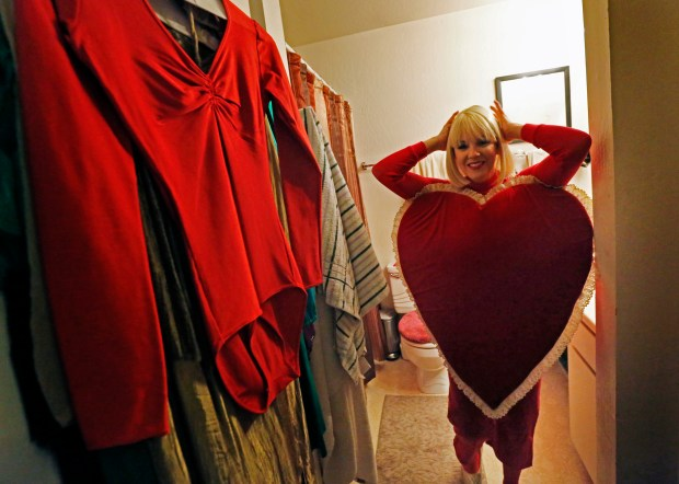 Entertainer Camille Larrea puts on her heart costume to get ready to sing her Valentine singing telegram act at her apartment in Concord, Calif., on Thursday, Jan. 12, 2017. (Laura A. Oda/Bay Area News Group)