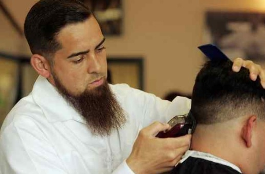Richard Hernandez, owner of The Barbershop in Rancho Cucamonga, cuts a client's hair on Friday, June 10, 2016.(STAFF FILE PHOTO)