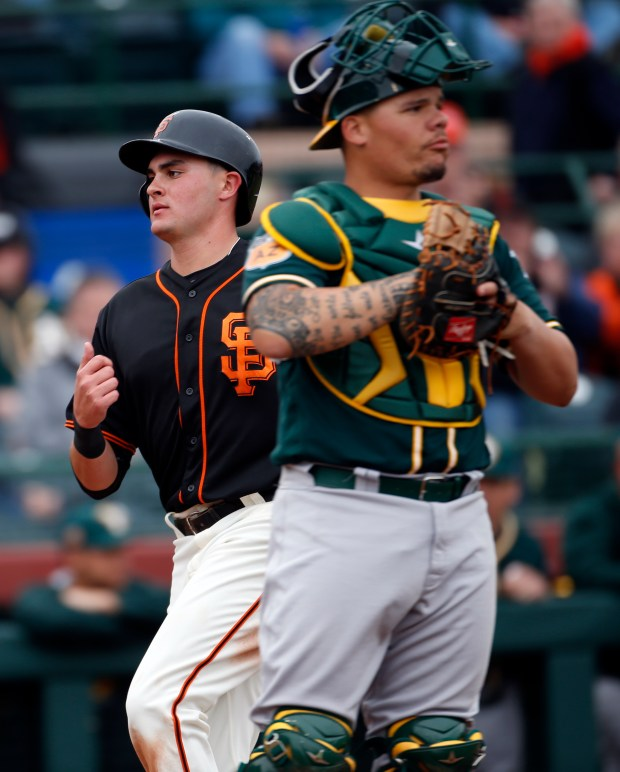 San Francisco Giants' Ryder Jones scores on a single by Michael Morse as the Oakland Athletics catcher Bruce Maxwell stands by in the 7th inning, Monday, Feb. 27, 2017, in Cactus League play at Scottsdale Stadium in Scottsdale, Az. (Karl Mondon/Bay Area News Group)