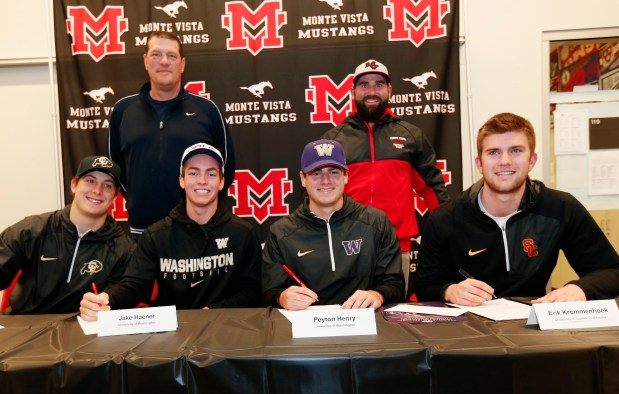 Nate Landman, Colorado, Jake Haener, University of Washington, Peyton Henry, Washington, and Erik Krommenhoek, USC, left to right, sign during letter of intent day at Monte Vista High School in Danville, Calif., on Wednesday, Feb. 1, 2017. Standing is Craig Bergman, football head coach and Matt Russi, defensive coordinator, left to right. (Gary Reyes/Bay Area News Group)