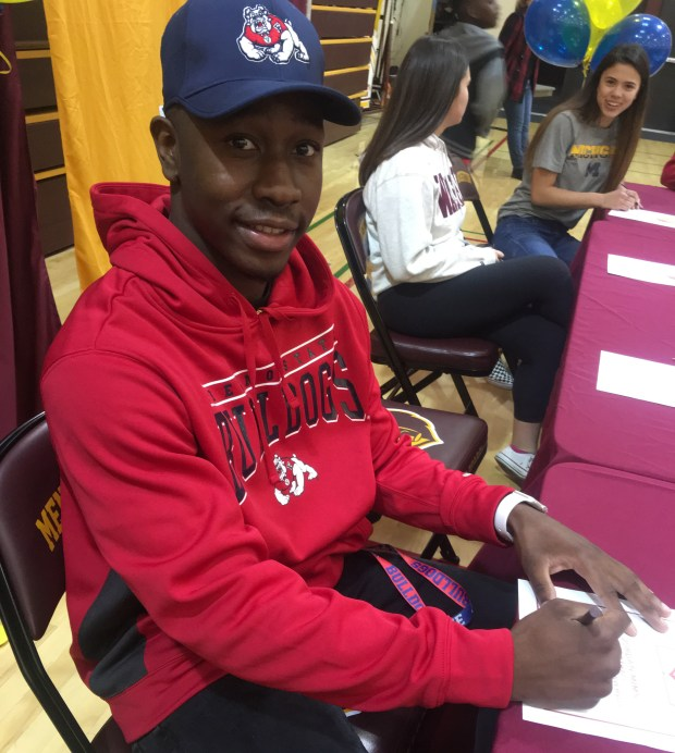 Menlo-Atherton senior Jordan Mims signs his letter of intent to play football at Fresno State during a ceremony at his school on Wednesday. (John Reid / Bay Area News Group)