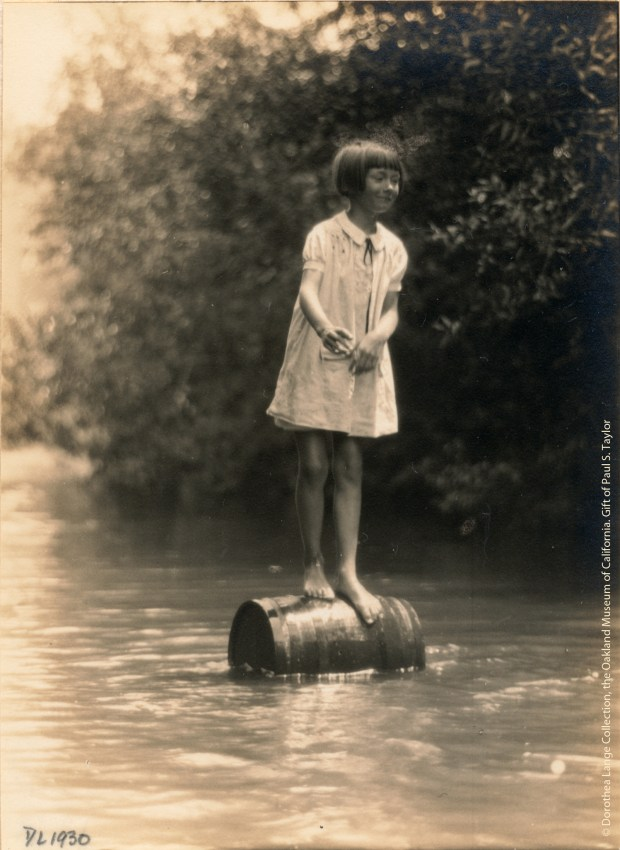 """""""Mary Louise Lovett, Soquel Creek, 1930 (Girl on Barrel)"""" is part of the exhibit """"Dorothea Lange: The Louise Lovett Collection,"""" the photographer's images from the 1930s, when she visited the farm of her friend Louise Lovett along Soquel Creek near Santa Cruz. The exhibit is at Peninsula Museum of Art in Burlingame through April 9, 2017. (Copyright Dorothea Lange Collection, the Oakland Museum of California. Gift of Paul S. Taylor)"""
