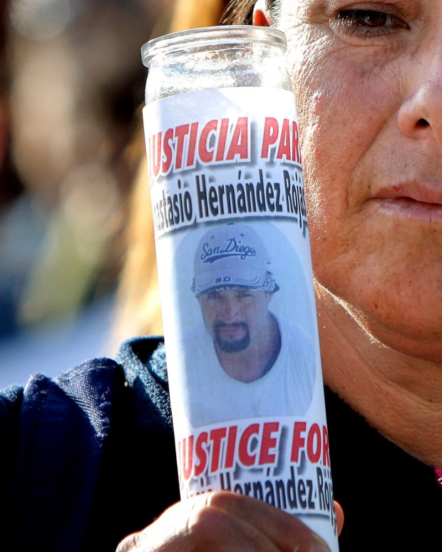 2010: A woman holds a votive candle with an image of Anastasio Hernandez during a protest at the San Ysidro border crossing. (AP Photo, File)