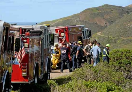Emergency workers evaluate how to retrieve the vehicle that drove off the road in the Marin Headlands. (Robert Tong — Marin Independent Journal)