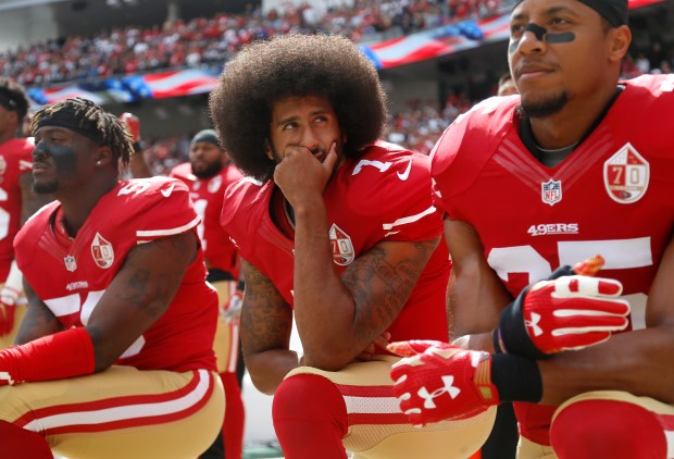 From left to right, San Francisco 49ers' Eli Harold (58), San Francisco 49ers quarterback Colin Kaepernick (7) and San Francisco 49ers' Eric Reid (35) kneel during the national anthem before their NFL game against the Dallas Cowboys at Levi's Stadium in Santa Clara, Calif., on Sunday, Oct. 2, 2016. (Nhat V. Meyer/Bay Area News Group)