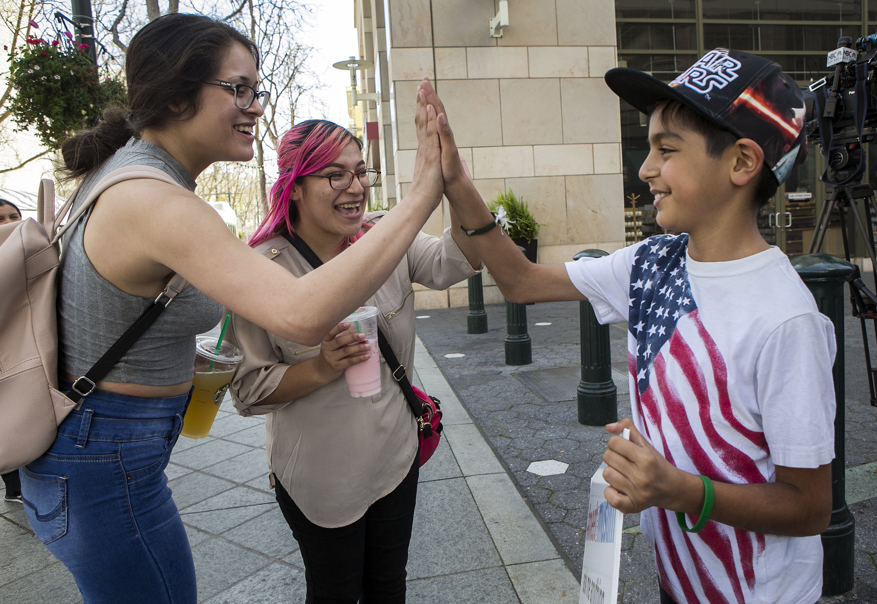 From left, Patricia Luna, 19, and Isabel Rangel, 20, both of San Jose, high five Rizwan Khan, 10, a Muslim from San Jose, during a