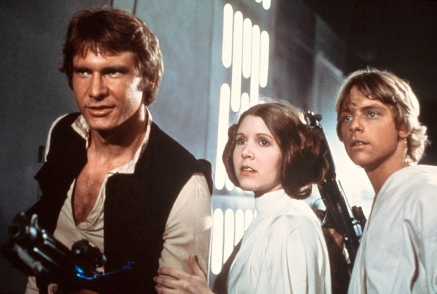 """This publicity film image provided by 20th Century-Fox Film Corporation shows, from left, Harrison Ford as Han Solo, Carrie Fisher as Princess Leia Organa and Mark Hamill as Luke Skywalker in a scene from the """"Star Wars"""" movie released by 20th Century-Fox in 1977. (AP Photo)"""