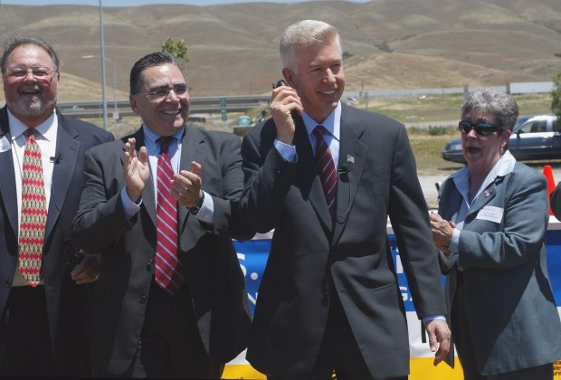 SAN JOSE MERCURY NEWS PHOTOGRAPH BY GARY REYES--05/19/2003 Governor Gray Davis uses a cell phone to signal Caltrans workers to remove the cones to officially open four brand new lanes on Highway 101 between San Jose and Morgan Hill on May 19, 2003. The project doubles the number of lanes and includes high-occupancy vehicle (HOV) lanes in both directions. The project completes 40 miles of uninterrupted carpool lanes on Highway 101 from Morgan Hill to Redwood City. The project was finished six months early. With Gov. Davis is, Donald Gage, VTA Board of Directors, San Jose Mayor, Ron Gonzales, and Jane Kennedy, VTA Board of Directors.