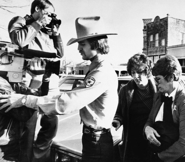 Feb. 16, 1984: Genene Jones, second from right, is escorted into Williamson County Courthouse in Georgetown, Texas. (AP Photo/Ted Powers, File)