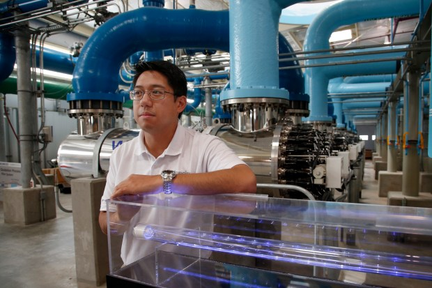 Paolo Baltar, an engineer for the Santa Clara Valley Water District, shows off the ultraviolet section, the final step in the water treatment process at the Silicon Valley Advanced Water Purification Center facility in San Jose. (Karl Mondon/Bay Area News Group)