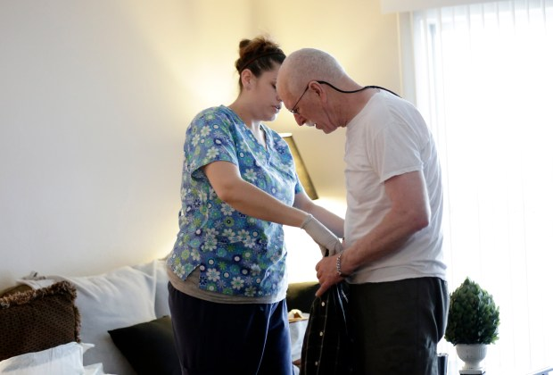 Medical assistant caregiver Amanda McGehee helps Steve Williams get dressed at home as he gets ready to go over to the Alzheimer's Activity Center near Valley Medical Center in San Jose, Calif., on Wednesday, May 24, 2017. Williams was diagnosed with early onset Alzheimer's disease seven years ago. (Josie Lepe/Bay Area News Group)