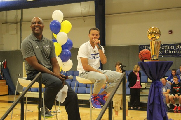 Stephen Curry, right, is joined by his former coach, Shonn Brown, while addressing the faculty and students at his alma mater, Charlotte Christian School, during a visit in the fall of 2015. (Courtesy Charlotte Christian School)