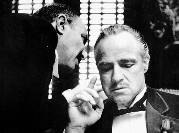 """FILE--By tradition, the Godfather cannot refuse a request on his daughter's wedding day, and Bonasera, portrayed by Frank Puglia, asks Don Corleone, portrayed by Marlon Brando, at right, for a favor in this scene from the 1972 movie """"The Godfather"""". Best-selling author Mario Puzo, creator of the fictional Corleone mob family and winner of two Oscars for his screen adaptations of his book ``The Godfather,'' died Friday, July 2, 1999. He was 78. (AP Photo/Paramount Pictures,file)"""