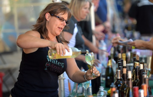 Diana Valencia, of Walnut Creek, with Wine Thieves, pours wine during the 20th annual Lafayette Art and Wine Festival in Lafayette, Calif., on Saturday, Sept. 19, 2015. The event draws more than 80,000 visitors and features four stages of music, a wine and beer tent, vendor booths, kids area of activities, and more. (Doug Duran/Bay Area News Group)