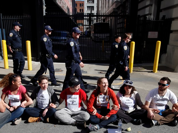 San Francisco police keep an eye on May Day protesters rallying for immigrant rights as they block an alley way behind the Immigration and Customs Enforcement (ICE) office, Monday, May 1, 2017, in San Francisco, Calif. (Karl Mondon/Bay Area News Group)