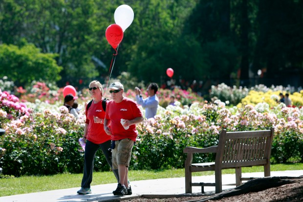 Patti Silva walks with her husband David in the Stroke Awareness Foundation Walk on Sunday, May 7, 2017, at the Municipal Rose Garden in San Jose, Calif. David Silva suffered a stroke this past December. They carried a red balloon to symbolize his recovery, and a white balloon for his mother who passed away after suffering a stroke in 1987. (Karl Mondon/Bay Area News Group)