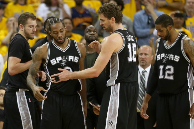 The San Antonio Spurs' Kawhi Leonard (2) gets up after the Golden State Warriors' Zaza Pachulia (27) fouled him as teammate Pau Gasol (16) looks on in the third quarter of Game 1 of the NBA Western Conference Finals at Oracle Arena in Oakland, Calif., on Sunday, May 14, 2017. Leonard left the game after making his free throws. (Ray Chavez/Bay Area News Group)