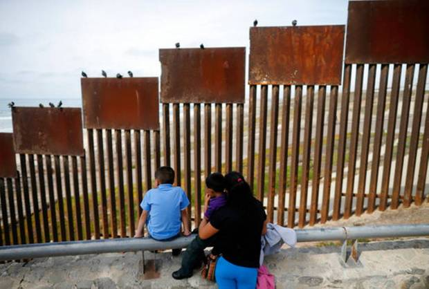 "In this March 2, 2016 file photo, a family looks towards metal bars marking the U.S. border where it meets the Pacific Ocean, in Tijuana, Mexico. Candidate Donald Trump's promise to build a ""big, beautiful wall"" on the Mexican border conjured images of an inpenetrable structure spanning 2,000 miles. Trump still insists he'll build the wall, but his top aides have made clear it won't be ""from sea to shining sea."" (Gregory Bull, File AP Photo)"
