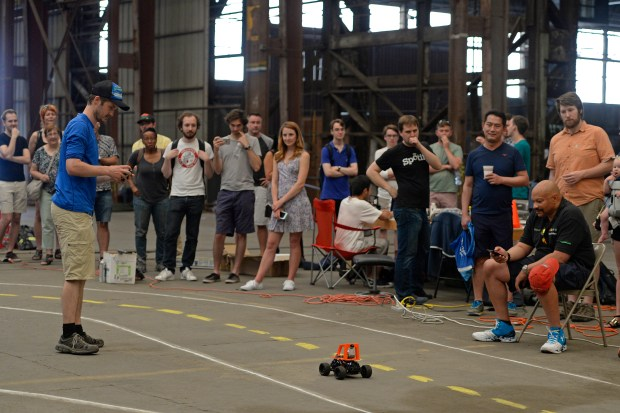 Will Roscoe, of Oakland, watches as his car takes off from the starting line as visitors and participants watch during a DIY Robocars event in Oakland, Calif. on Saturday, June 17, 2017. About 30 participants converged in a warehouse and attempted to get their mini self-driving vehicles to complete a lap on a makeshift road course. The monthly event started in January of this year. (Jose Carlos Fajardo/Bay Area News Group)