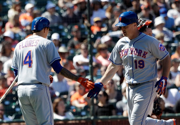 New York Mets' Jay Bruce, right, is met at the plate by teammate Wilmer Flores, left, after Bruce's two-run home run during the eighth inning of a baseball game against the San Francisco Giants Sunday, June 25, 2017, in San Francisco. (AP Photo/Marcio Jose Sanchez)