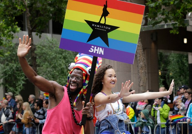 "Broadway musical ""Hamilton"" cast members Michael Luwoye, left, and Solea Pfeiffer wave during the Pride parade in San Francisco, Sunday, June 25, 2017. (AP Photo/Jeff Chiu)"