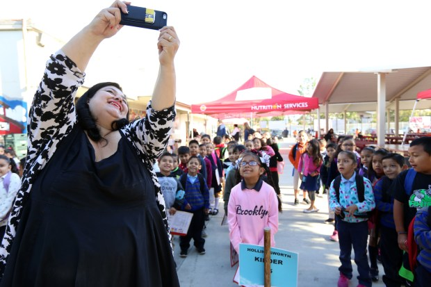 Madison Elementary Principal Lisa Gonzales-Solomon snaps a selfie with students one morning before class in Santa Ana. The Santa Ana Unified School District is one of 15 CALmatters studied to understand how well the state's funding system is working.