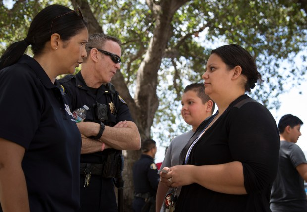 Lt. Mike Sullivan and crime prevention supervisor, Esther Mota, left, talk with Gabriel Cruz, 8, and his mother, Violet Martinez, as San Jose Police hosted a community event in the city's crime & gang-riddled Hoffman Via Monte neighborhood in San Jose, Calif., Saturday, June 3, 2017. The event is the culmination of a pilot program that the PD's crime prevention unit has led in this troubled neighborhood for the past year. (Patrick Tehan/Bay Area News Group)