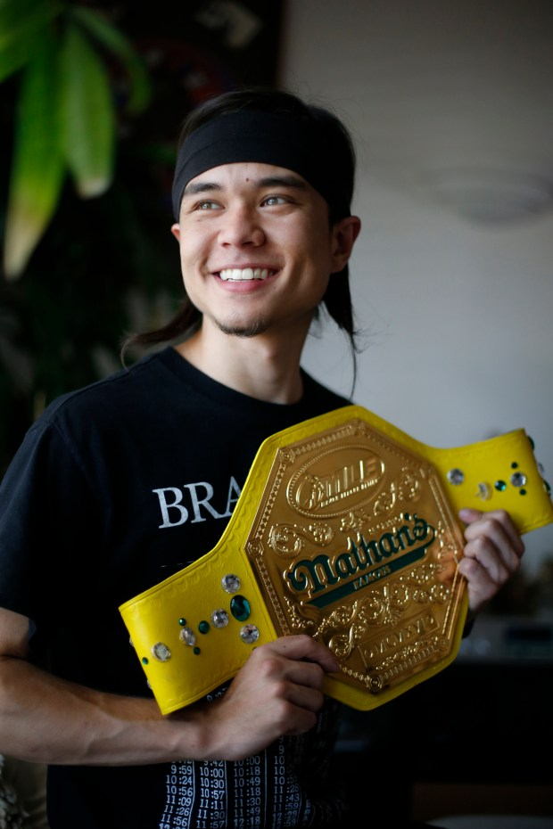 Matt Stonie, 23, the world's newest competitive eating champion, holds the Nathan's Famous hot dog eating title belt at his home in San Jose, Calif., on Thursday, July 16, 2015. (Josie Lepe/Bay Area News Group)