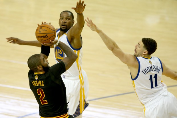 The Golden State Warriors' Kevin Durant (35) and Klay Thompson (11) defend Cleveland Cavaliers' Kyrie Irving (2)) in the fourth quarter of Game 2 of the NBA Finals at Oracle Arena in Oakland, Calif., on Sunday, June 4, 2017. (Ray Chavez/Bay Area News Group)