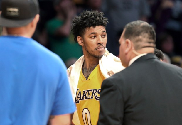 Los Angeles Lakers guard Nick Young is escorted off the court after he and two other players were ejected after a shoving match that started after Young took a hard foul from Milwaukee Bucks' Malcolm Brogdon during the third quarter of an NBA basketball game in Los Angeles on Friday, March 17, 2017. (AP Photo/Reed Saxon)