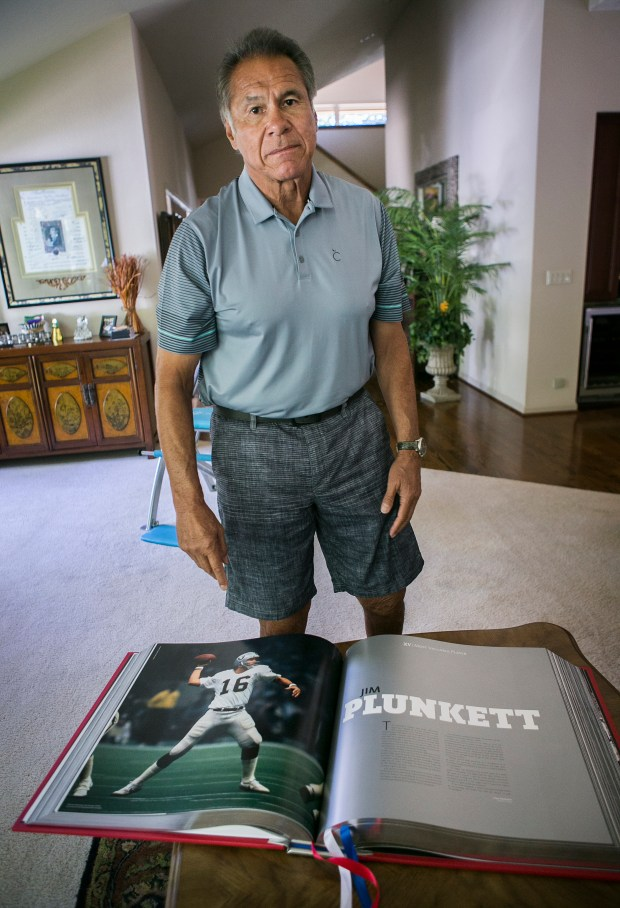 Former Stanford, 49ers and Raiders Quarterback Jim Plunkett displays a game photo of himself as the Raiders Quarterback from the XL Super Bowl Opus MVP Edition book at his home in Atherton, California, on Wednesday, July 19, 2017. The book is only available to MVP players and owners of the Super Bowl. (LiPo Ching/Bay Area News Group)