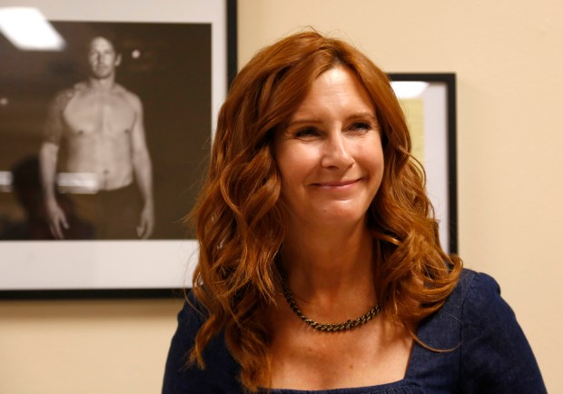 """Tabitha Soren, former MTV reporter and now photographer, smiles as she listens to a question from guests in front of photographs she took of former Oakland Athletic's John Baker on display during the opening reception of her exhibition called """"Fantasy Life"""" at San Francisco City Hall in San Francisco, Calif. on Thursday, July 20, 2017. (Nhat V. Meyer/Bay Area News Group)"""