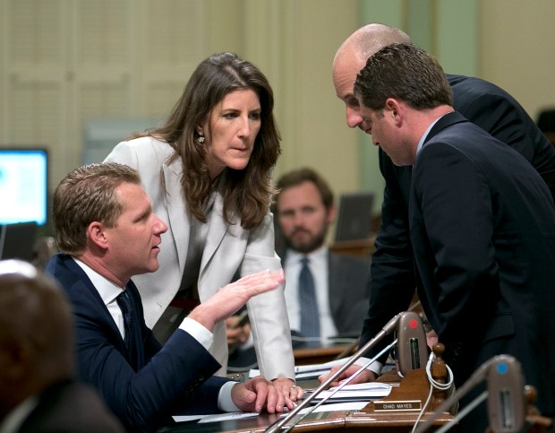 In this photo taken Monday, July 17, 2017, Assembly Republican Leader Chad Mayes, of Yucca Valley,, left, huddles with GOP Assembly members Catharine Baker, of San Ramon, Heath Flora, of Ripon, third from left, and Jordan Cunningham, of Templeton, as the Assembly debates a climate change measure in Sacramento, Calif. Mayes and and the other three lawmakers voted to extend California's cap-and-trade program despite opposition from much of the GOP base. (AP Photo/Rich Pedroncelli)