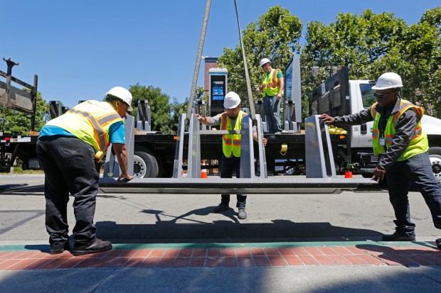 An installation team works on installing the bike racks for the Ford GoBikes outside City Hall in Emeryville, Calif., on Thursday, July 6, 2017. Ford GoBikes, formerly known as Bay Area Bike Share, is in the process of installing stations throughout the East Bay as part of its ten-fold expansion from 700 bikes to 7,000. (Laura A. Oda/Bay Area News Group)