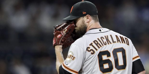 San Francisco Giants relief pitcher Hunter Strickland wipes his face with his glove during the eighth inning against the San Diego Padres in a baseball game Friday, July 14, 2017, in San Diego. (AP Photo/Gregory Bull)
