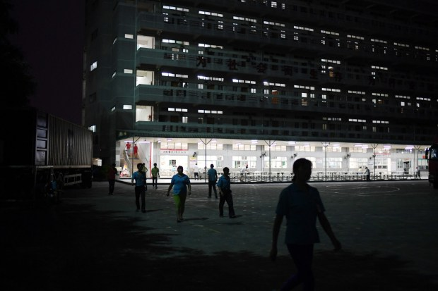 Workers in Dongguan, China, walk past dormitory buildings last September at the Huajian shoe factory, which has made shoes for Ivanka Trump and other brands. (Greg Baker/Agence France-Presse via Getty Images)