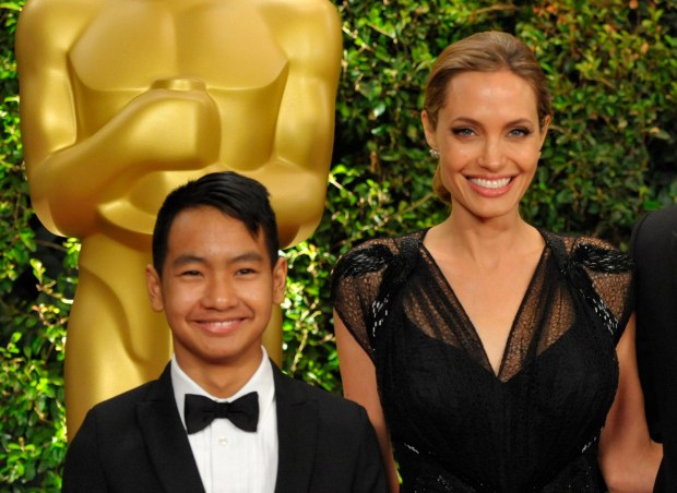 """FILE - This Nov. 16, 2013 file photo shows Maddox Jolie-Pitt, with Angelina Jolie on the red carpet at the 2013 Board of Governors of the Academy of Motion Picture Arts and Sciences' Governor Awards, in Los Angeles. Cambodia's King Norodom Sihamoni will preside over the premiere of Angelina Jolie's film based on a memoir from a Khmer Rouge survivor. Queen Mother Norodom Monineath Sihanouk will also attend the showing of """"First They Killed My Father,"""" on Saturday at the centuries-old Angkor Wat temple complex, an official said. Jolie directed the Khmer-language film on location in 2015-16. (Photo by John Shearer/Invision/AP, File)"""