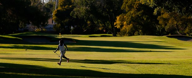 A young golfer runs across a fairway during a late evening round on the Marina Course at the Monarach Bay Golf Club on Wednesday, July 5, 2017, in San Leandro, Calif. (Aric Crabb/Bay Area News Group)