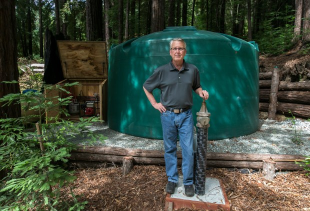 Scott Jamar poses for a portrait in front of the 4995 gallon water storage tank he installed on his home's property to fight potential wildfires in Los Gatos, California, on Saturday, July 15, 2017. At left, Jamar planted a Redwood seedling to help cover the tank. (LiPo Ching/Bay Area News Group)