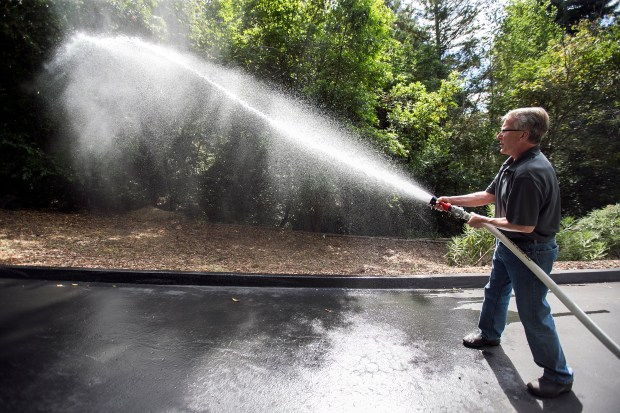 Scott Jamar demonstrates the reach of his firehose's water spray that's being pumped from a water tank he installed on his home's property in Los Gatos, California, on Saturday, July 15, 2017. Jamar installed a 4995 gallon water storage tank on his home's property to fight potential wildfires. (LiPo Ching/Bay Area News Group)